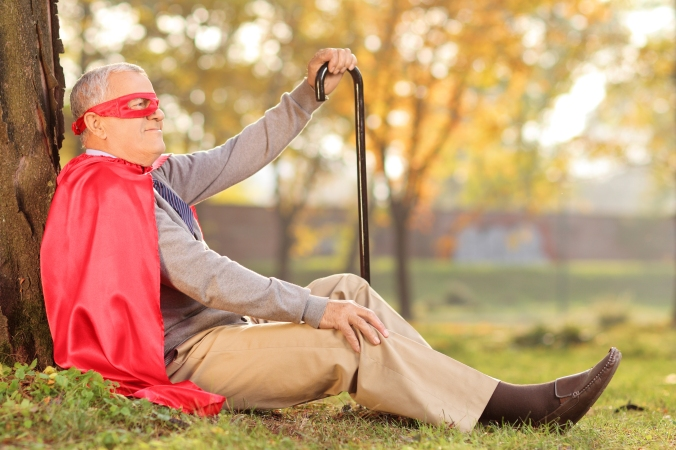 Senile old man sitting outdoor in superhero costume